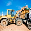 Stock Photo: Wheel loader machine loading dumper truck