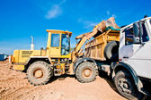 Wheel loader machine loading dumper truck — Stock Photo