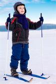 Smiling kid boy skier standing in snow — Stock Photo