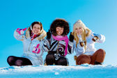Three cheerful girls outdoors in winter showing a thumbs up — Stock Photo