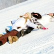 Young positive girls lying on the snow - Stock Photo