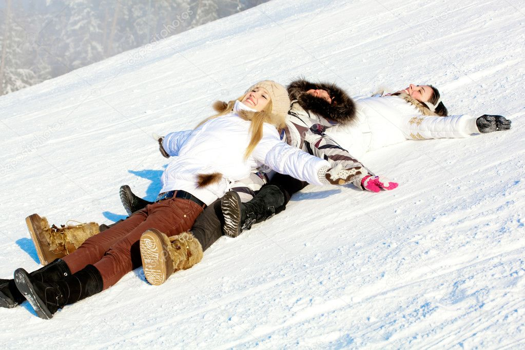 Happy girls lying down on the snow at slope in winter — Stock Photo #8802681