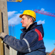 Stock Photo: Construction worker checking vertical level of house wall
