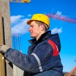 Construction worker checking vertical level of house wall — Stock Photo #8859309