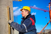Construction worker checking vertical level of house wall — Stock Photo