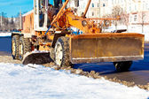 Road scraper removing snow — Stock Photo