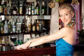 Young beautiful blonde woman at a bar counter — Stock Photo