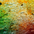 Rust Grunge textured background under a layer of clay with shades of green, red, yellow. — Stock Photo