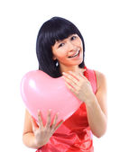 Attractive smiling woman isolated on white with heart balloon — Stock Photo