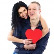 Young adult couple with red heart on white background — Stock Photo