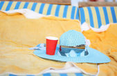 Summer blue hat and glasses on the lounge — Stock Photo