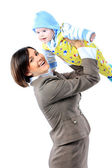 Business woman in suit carrying baby in arms. — Stock Photo