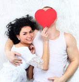 Lovely couple holding red heart together lying in a bed — Stock Photo