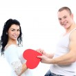 Beautiful young love couple with a big red heart — Stock Photo