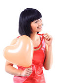 Young woman with a heart-shaped balloon in her hands — Stock Photo