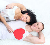 Lovely couple holding red heart together lying on the floor — Stock Photo