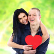 Happy couple with heart smiling outdoors — Stock Photo