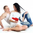Happy young adult couple with red heart on the floor — Stock Photo