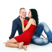 Beautiful young love couple sitting on the floor with a big red heart — Foto de Stock