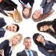 Stock Photo: Group of business standing in huddle, smiling, low angle view
