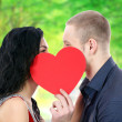 Happy couple with heart kissing outdoors — Stock Photo
