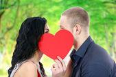Счастливая пара с сердцем, поцелуи на открытом воздухе — Стоковое фото