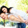 Loving couple enjoying together while piggyback ride outdoors — Stock Photo