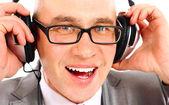 Usmíval se podnikatel sluchátka při pohledu na fotoaparát, poslech hudby — Stock fotografie