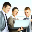 Stock Photo: Young businesswoman with her collegues using laptop
