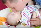 The young father kisses the small daughter — Stock Photo
