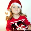 The little girl in a New Year's hat with a gift — Stock Photo #8020309