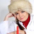 The young beautiful girl in a fur cap with a candle — Stock Photo #8020687