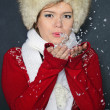 The young beautiful girl in a cap blows off snow from hands — Stock Photo #8020819