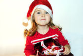 The little girl in a New Year's hat with a gift — Stock Photo