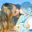 Stock Photo: Small beautiful girl kisses mum on seacoast in autumn