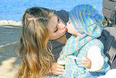La piccola ragazza bella baci mamma sul litorale in autunno — Foto Stock