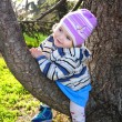 Stock Photo: The small beautiful joyful girl sits on a tree branch
