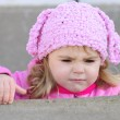Portrait of the small beautiful indignant girl with in a pink ca — Stock Photo
