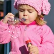 Stock Photo: The small beautiful girl in pink clothes with soap bubbles