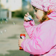 The small beautiful girl in pink clothes with soap bubbles — Stock Photo