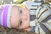 The small beautiful girl lies on a tree branch — Stock Photo