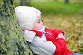 Küçük kız ağaca sonbahar park yakınında oturuyor — Stok fotoğraf