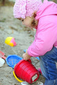 The small beautiful girl in pink clothes plays sand — Stock Photo