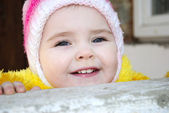 The small beautiful girl looks out behind a parapet — Stock Photo