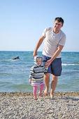 Küçük kız babası ile sahil üzerinde yürür — Stok fotoğraf