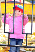 The little girl with a yellow leaflet in autumn park — Stock Photo