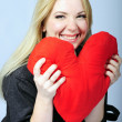 Beautiful girl blonde with red heart in hand — Stock Photo #8572846