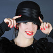 Beautiful bright girl in black hat — Stock Photo
