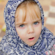 Portrait of the small beautiful girl in a dark blue scarf — Stock fotografie