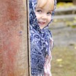 The small beautiful girl in a dark blue scarf looks out from rou — Stock Photo